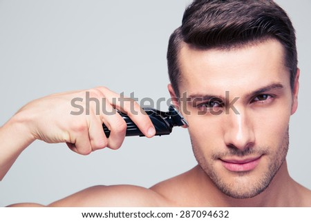 Young happy man shaving with electric razor - stock photo