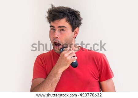 Young happy man shaving with electric razor in the morning - dental hygiene - stock photo