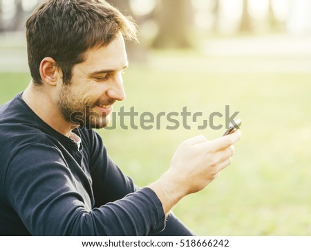 Young happy man sitting in the park and using smartphone.