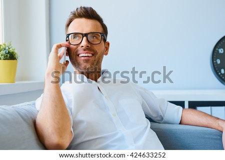 Young happy man sitting relaxed on sofa and talking on the phone - stock photo