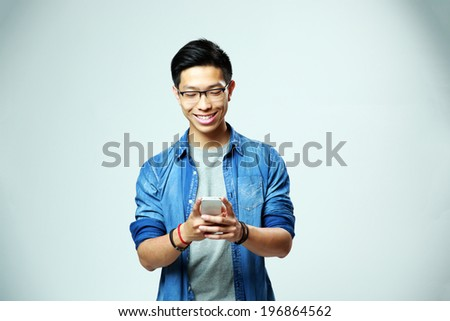 Young happy man using smartphone on gray background - stock photo
