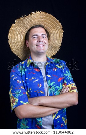 young happy man with a hawaiian shirt on black background - stock photo