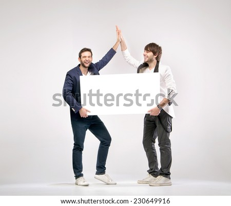 Young happy man with empty board - stock photo