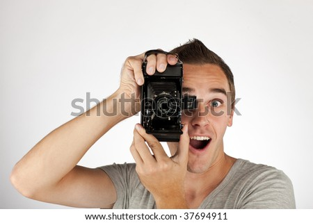 Young happy man with old camera. - stock photo