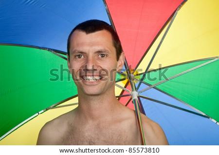 young happy man with umbrella, studio picture - stock photo