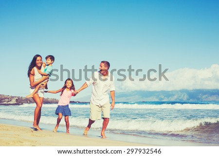 Young Happy Mixed Race Family Having Fun on the Beach Outdoors - stock photo