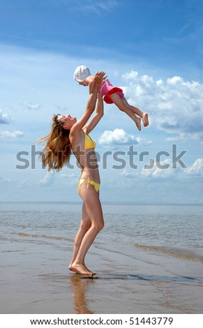 Young happy mother abandons a baby on a beach - stock photo