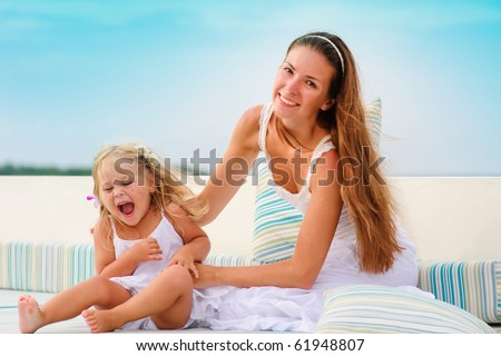 Young happy mother and her toddler pretty daughter have a fun in beach cafe - stock photo