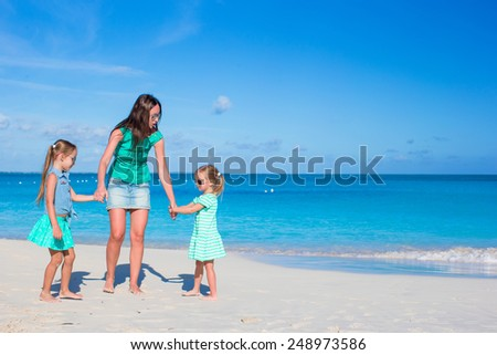 Young happy mother and little girl having fun during beach vacation