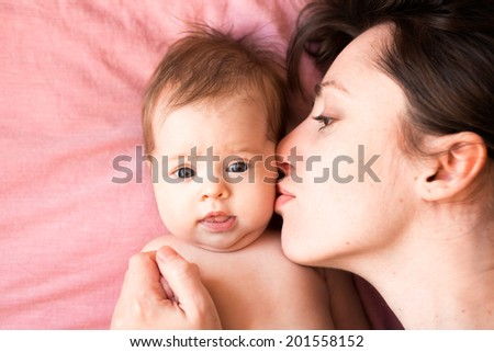 Young happy mother kissing cute newborn baby - stock photo