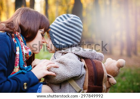 Young Happy Mother Talking to Son while Walking in the Park at the Day. Close up Portrait of Family. Copy Space for Text. - stock photo