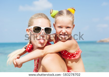 Young happy mother with little girl on her back. Happy family having fun at beach in summer - stock photo