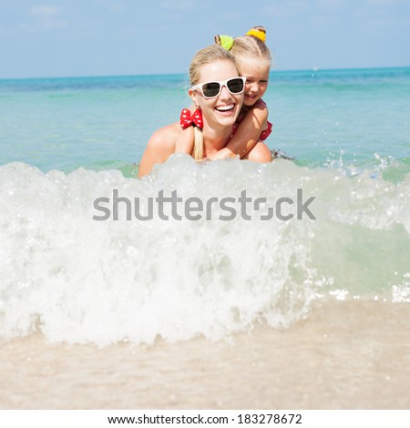 Young happy mother with little girl on her back. Happy family swimming in summer Outdoors - stock photo