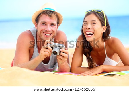 Young happy multicultural couple on beach having fun laughing during summer holiday vacation. Caucasian hipster man with retro vintage camera and asian woman joyful. - stock photo