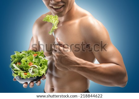 Young happy muscular man eating a salad - stock photo