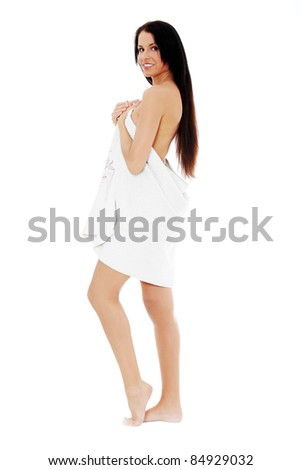 Young happy naked woman covering her self with towel on white background. - stock photo