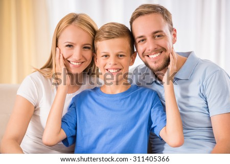 Young happy parent and their teenage son are posing at home, smiling. - stock photo