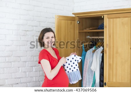 Young happy pregnant girl holding baby clothes near wardrobe