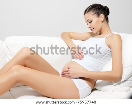 Young happy pregnant woman sitting on sofa
