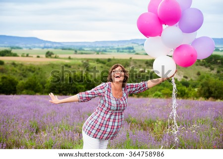 Young happy pregnant woman with balloons outdoors - stock photo