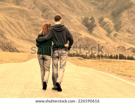Young happy romantic couple (caucasian man and woman) walking along the asphalt road among beautiful mountain area (Altai region, Russia) embracing each other.