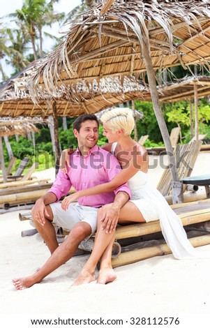 Young happy romantic sitting on sunbed on the sandy tropical beach with palm trees. Bride and groom. Wedding and honeymoon concept. - stock photo
