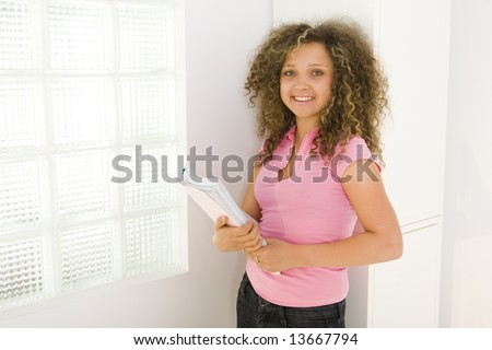 Young happy schoolgirl standing near window and leaning for school locker. She's holding notebooks. Looking at camera. - stock photo