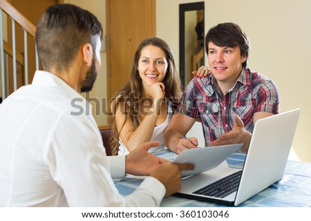 Young happy seller try hard to sign a contract with merried couple