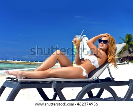 Young happy sexy woman lying relaxing tropical sea beach sand with alcohol cocktail pina colada drink laughing in white bikini and sunglasses