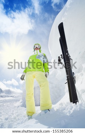Young happy skier woman standing with ski put in snow huge high snowdrift and mountain on background - stock photo