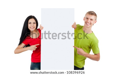 young happy smile couple standing hold pointing finger at a blank board, handsome guy attractive girl wear green red shirt, isolated over white background, studio shoot - stock photo
