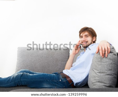 Young happy smile man phone call on sofa in living room, at home - indoors, guy lying talking cellphone - stock photo