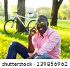 Young happy smiling african american with mobile phone and bicycle behind him in a park - stock photo