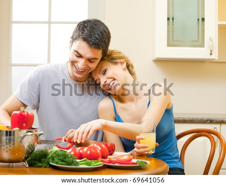 Young happy smiling amorous couple cooking together at home
