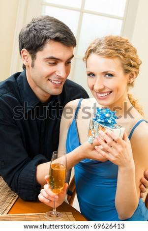 Young happy smiling amorous couple with gift and champagne at home - stock photo
