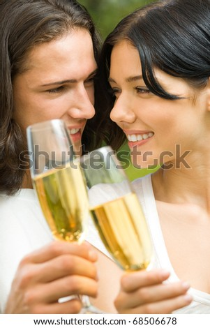 Young happy smiling attractive couple celebrating with champagne together, outdoor