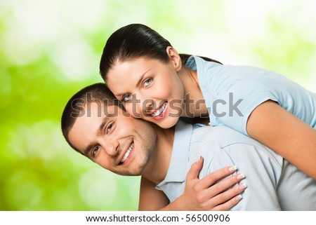 Young happy smiling attractive couple, outdoors - stock photo