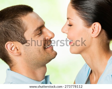 Young happy smiling attractive couple, outdoors, with copyspace area for text or slogan - stock photo