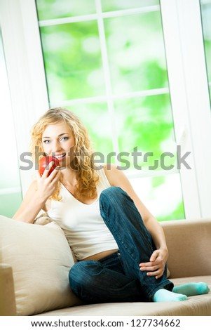 Young happy smiling beautiful blonde woman with apple, with copyspace - stock photo