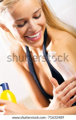 Young happy smiling beautiful tanned woman applying sun protection cream on sea beach - stock photo