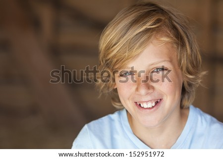 Young happy smiling blond boy child aged about twelve or early teenager   - stock photo