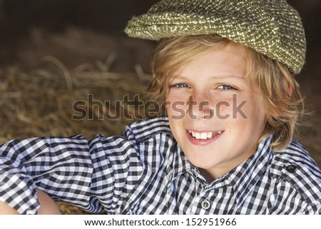 Young happy smiling blond boy child aged about twelve or early teenager wearing a plaid shirt and flat cap sitting on hay or straw bales - stock photo