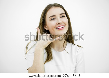 Young happy smiling brunette woman with call me gesture, against white background - stock photo