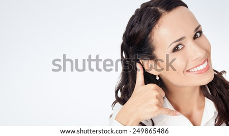 Young happy smiling business woman with call me gesture, against grey background, with copyspace