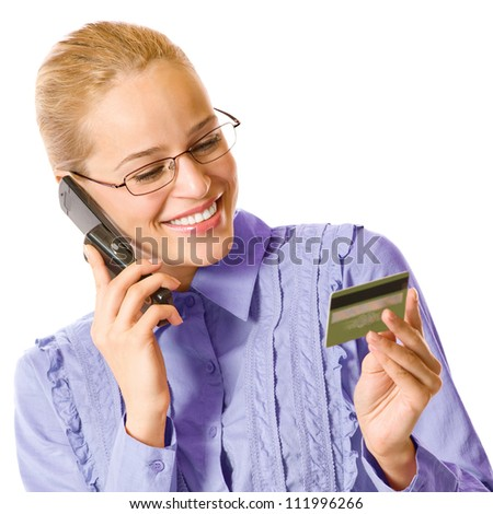 Young happy smiling business woman with plastic card, on cellphone, isolated over white background - stock photo