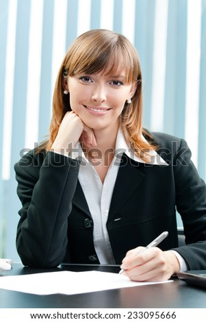 Young happy smiling businesswoman working with document at office - stock photo