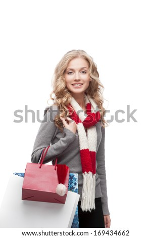 young happy smiling casual  blond woman holding  shopping bags isolated on white