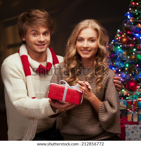 young happy smiling casual couple holding red gift over christmas tree and lights on background. warm light - stock photo