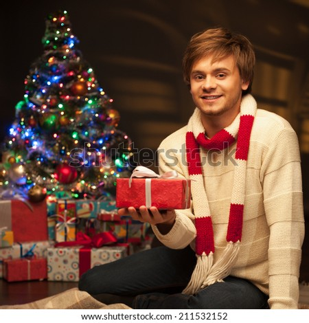 young happy smiling casual man holding red gift over christmas tree and lights on background. warm light - stock photo