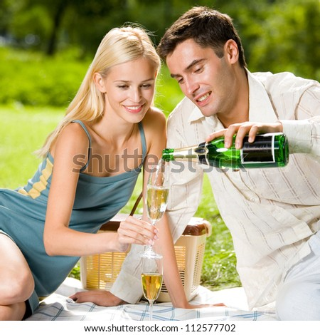 Young happy smiling cheerful attractive couple celebrating with champagne, outdoor - stock photo